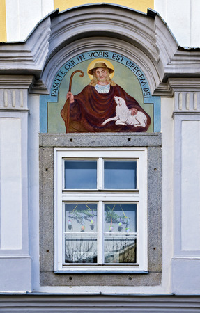 paschal lamb: fresco of a shepherd with a lamb and the inscription pascite oui in vobis est gregem dei above a easter decorated window, Freistadt, Austria Editorial