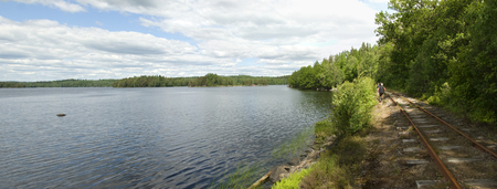 narrowgauge: Panoramic view across the lake Hjortosjoen and the track of a heritage narrow-gauge railway in the south of Sweden, Virserum, Smaland.