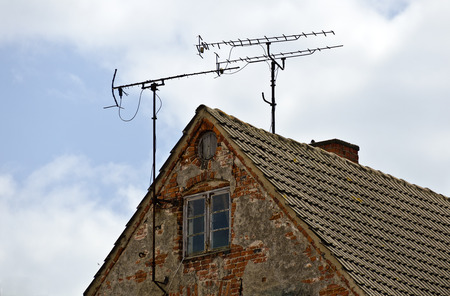pediment: antennas on the roof of an old desolate house Stock Photo