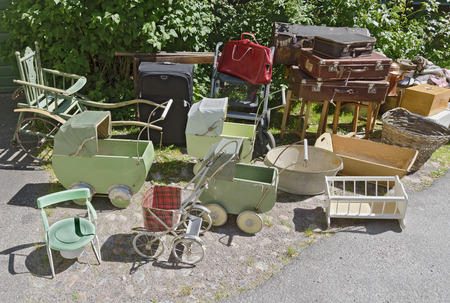 rummage: old pushcars, furniture for children and luggage at a junk dealer at Vaestervik, Sweden Stock Photo