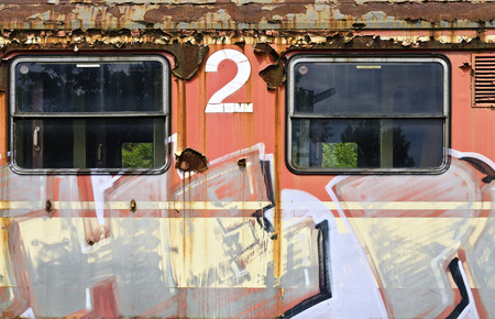 sprayed: orange wall of an off service second class  waggon with two windows, sprayed with graphic characters