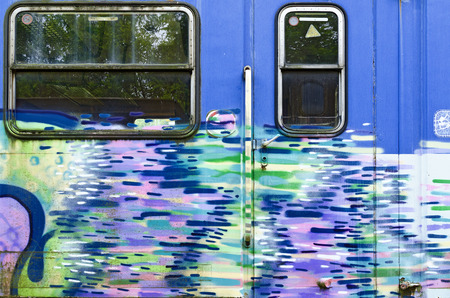 sprayed: blue wall of an off service waggon with door and window, sprayed with colorful pattern