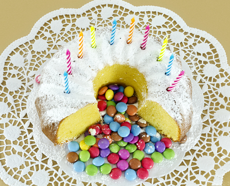 Partly sliced ring-shaped sponge cake with birthday candles  and colour-varied sugar-coated chocolate confectionery strewed with powdered sugar