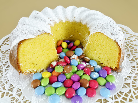 Partly sliced ring-shaped sponge cake and colour-varied sugar-coated chocolate confectionery strewed with powdered sugar Stock Photo