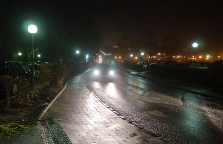 street wet from rain with car traffic and parking signs at night, Bath Tatzmannsdorf, Austria
