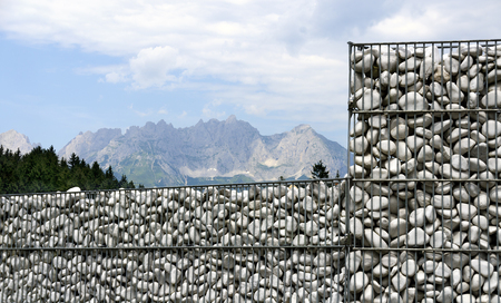 gabion filled with white stones and the mountain range of the Kitzbuehler alps in the back, Tirol, Austria Stock Photo