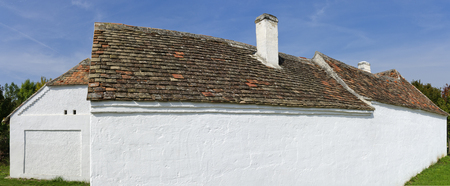 old farm house with Clay roof tiles and whitewashed wall of clay plaster in the sun