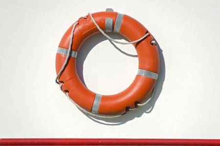 orange life bouy with rope on the white side wall of a ship