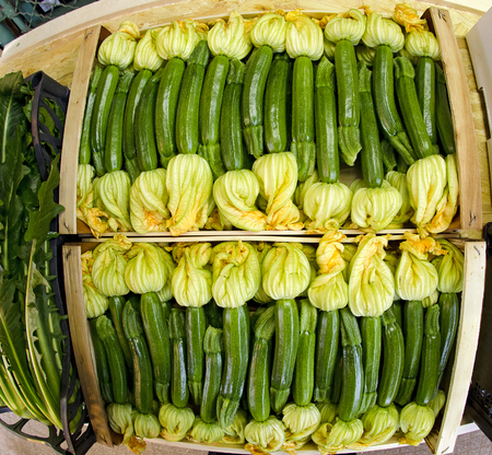 lug: wooden  crate with little courgettes with blossoms at a market stall Stock Photo