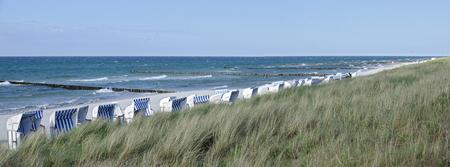 草に覆われた堤防、groynes、ツィングスト、ドイツで保護されたバルト海の椅子と白いビーチで砂浜など