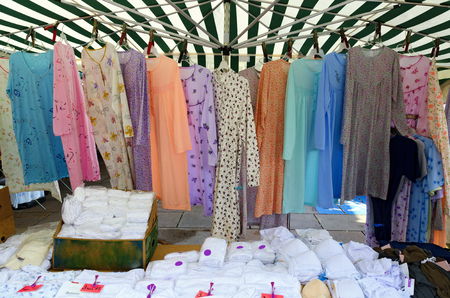 stall of a pedlar with  clothing on a traditional outdoor commercial fair (Simonimarket) at the city of Tulln, Austria