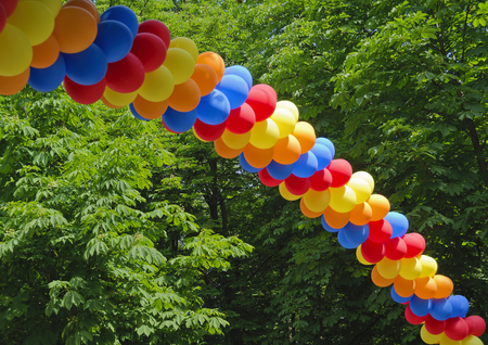 arch made from colorful balloons hovering in front of forest trees Stock Photo