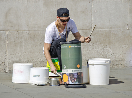 LONDON, UNITED KINGDOM - APRIL 30, 2013: street musician drumming on container made from plastiqe and cardboard