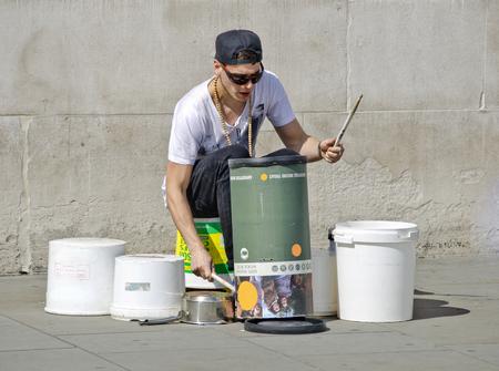 LONDON, VEREINIGTES KÖNIGREICH - 30. APRIL 2013: Straßenmusiker, der auf den Behälter trommert, der von plastiqe und von der Pappe gemacht wird