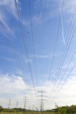 rijen van machtspolen met veelvoudige machtslijnen met hoog voltage tegen de blauwe hemel Stockfoto