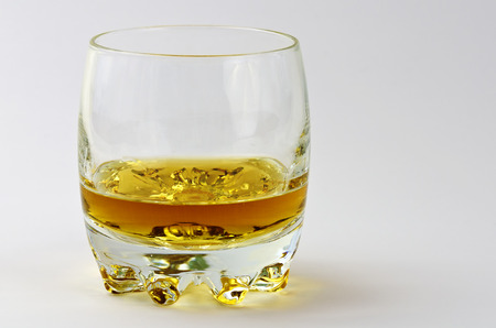 Tumbler partly filled with amber-coloured whisky on light background
