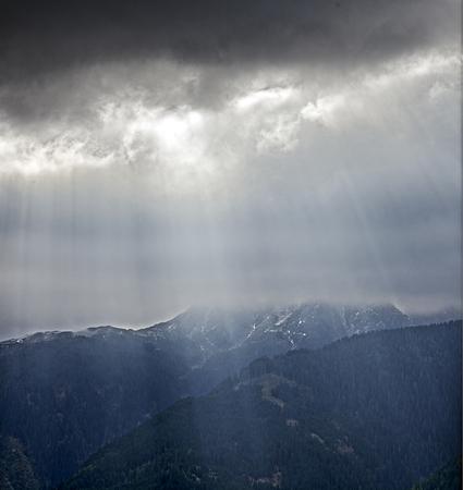 Sunbeams fall through storm clouds on a mountain landscape in Tyrol, Austria; Sun rays falling through thunder clouds on a mountain landscape at Tyrol, Austria