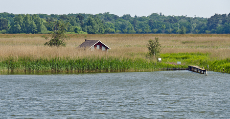 little house with bathing place and jetty at a reed belt on a lagoon Stock Photo