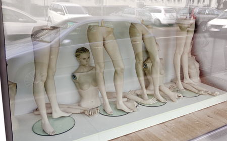 Shopping window with parts of undressed fashion dolls during re-decoration