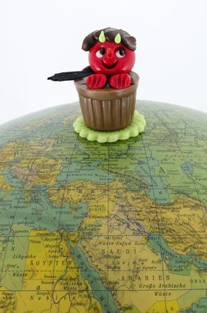 Bonbon shaped like an incubus on an old globe