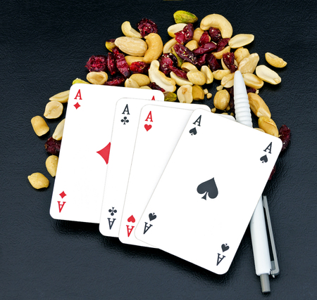 poker hand Four of a kind without kicker and white ballpen on trail mix from nuts and dry berries called student feed