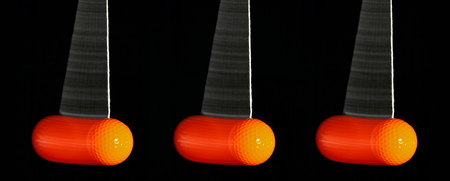 three swinging orange coloured golf balls before black background