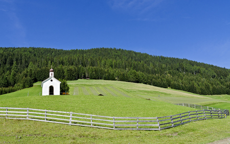chapel on a fenced meadow at a mountain slope