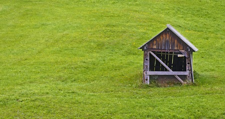 green pasture slope with old wooden barn