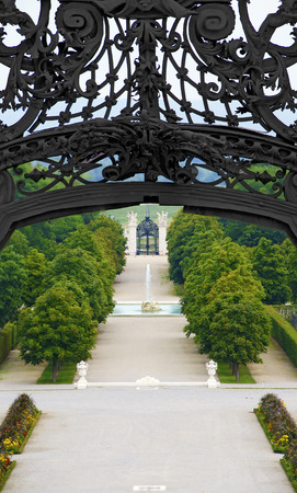 view through a portal made by wrought iron to a baroque garden with a fountain at the palace Schlosshof, Austria 新聞圖片