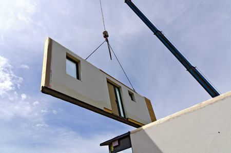 exterior wall of a prefabricated house hanging on a truck-mounted crane Stock Photo