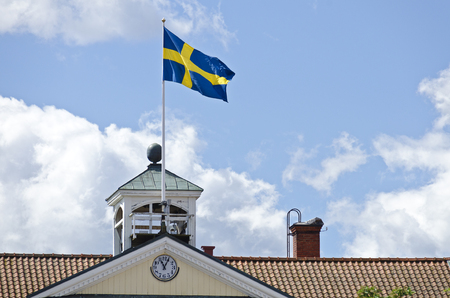 swedish flag on a gable of a wooden house with a clock