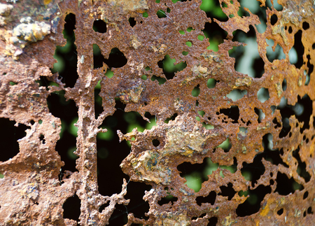 near view of a corroded rusty hull with holes of a steel barrel Stock Photo