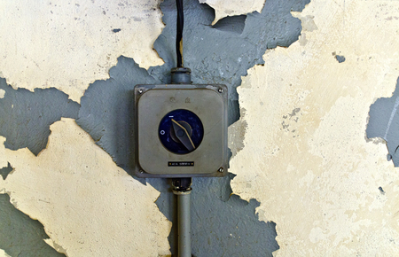 old switch for high voltage current on a wall with peeling paint