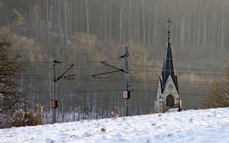 church spire behind a overhead wiring of a railroad at winter, Pressbaum, Austria Stock Photo