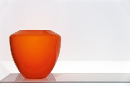 Still life of an orange glass vase on a gray board before a white wall