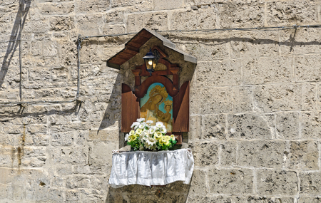 Wall shrine with picture of a madonna and flowers at Bari, Italy