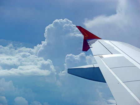 wing  with red winglet at flight before clouds