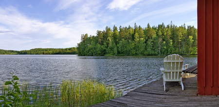 the swedish lake Gissen with pier and garden chair in the light of the afternoon sun Stock Photo