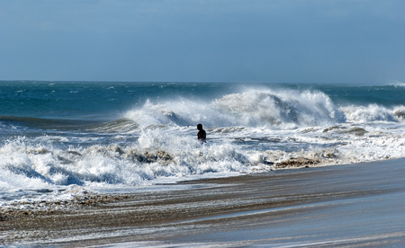 Silhouette of a bather in  the foaming waves of the atlantic ocean at the beach area of Grand Canary, Spain
