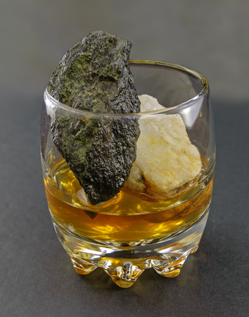 still-life made from a tumbler glass with Whisky and small rocks