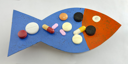 medicine from a pharmaceutical kit, pills, tablets, dragees and capsules on a plate shaped like a fish