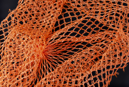 torn flexible mesh  for packing goods made from orange plastic filaments