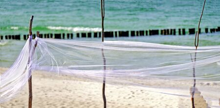 Waving transparent white veil at a sandy beach with Baltic Sea and Groyne in the back, Germany Stok Fotoğraf