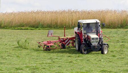 farm tractor with hay tedder turning the fresh cut grass