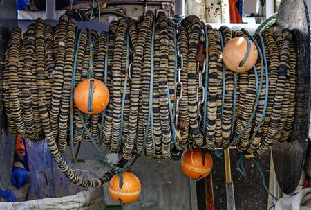 floating line with orange floatings balls of a fishnet coiled on a winch on board of a fishing boat at Sassnitz, Germany