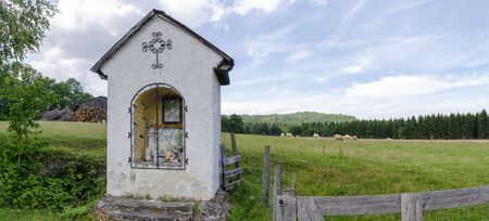 Landscape with fenced meadow and brick-build traditional wayside shrine at Harbach, Austria