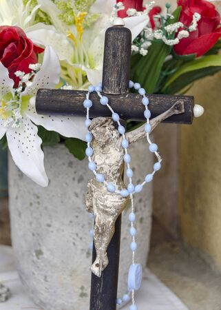 small old damaged crucifix before a bunch of flowers