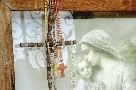 crosses and rosaries hanging on an old picture of a woman mit child