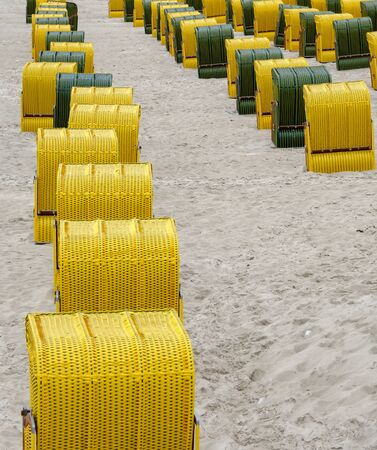 rows of beach chairs of yellow or black colors at the sand beach of the seaside resort Binmz, Germany