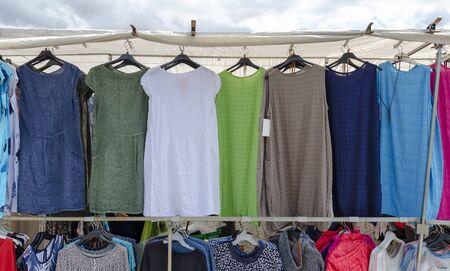 Cheap womens dresses hang at a market stall in Vetlanda, Sweden; cheap dresses for ladies hanging on a market stall at Vetlanda, Sweden 版權商用圖片
